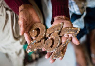 Atingida de Bento Rodrigues guardou em um pano os números da casa que foi destruída pela lama.